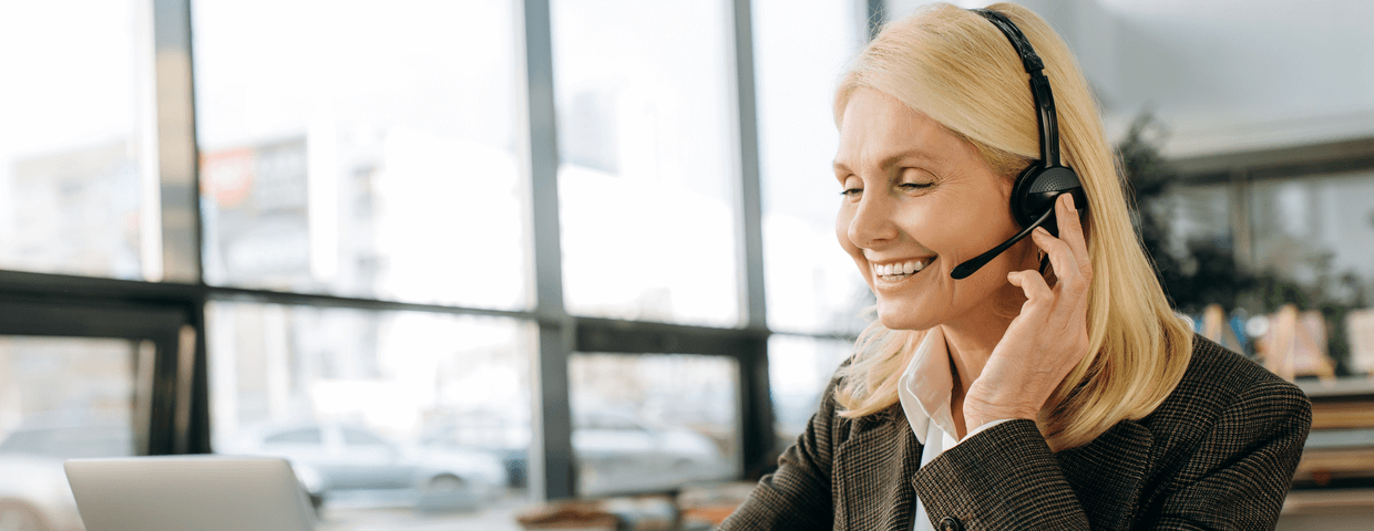 Business woman smiling, with hand on headset in open bright office. Cars and other buildings in blurred background.