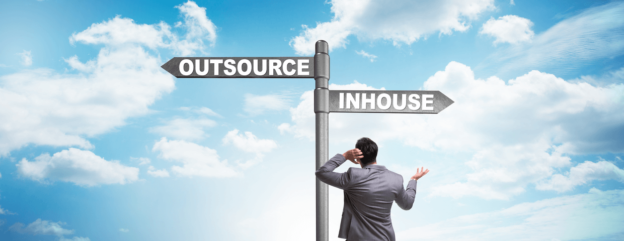Businessman at two way sign deciding between outsourcing and in-house. Blue sky with clouds in background