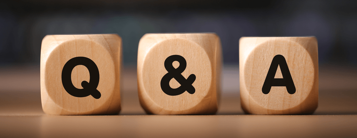 Wooden blocks that have the letters Q and A on them on a wooden table