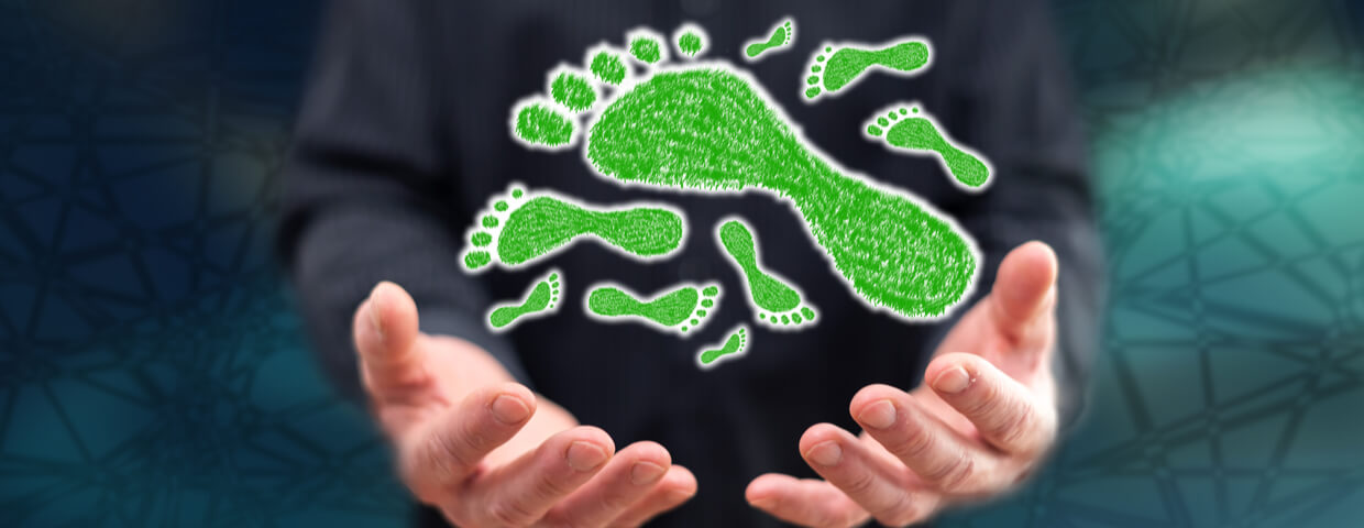 Carbon footprint concept above the hands of a man in background