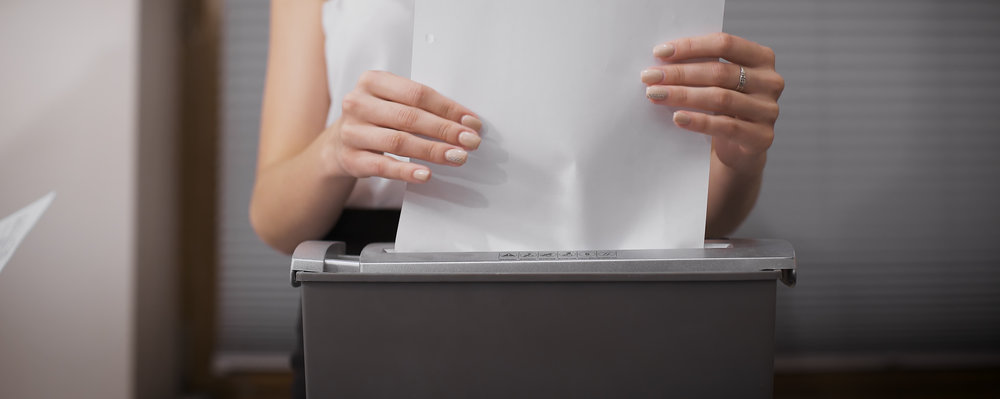 Woman feeding paper into a shredder
